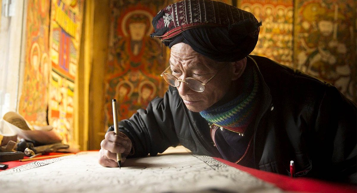 A man dressed as an ancient scribe wearing glasses, writing with a quill pen on parchment.